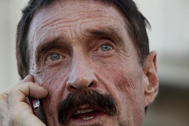 Software company founder John McAfee talks on his mobile phone after a press conference outside the Supreme Court in Guatemala City, Tuesday, Dec. 4, 2012. McAfee, 67, who has been identified as a