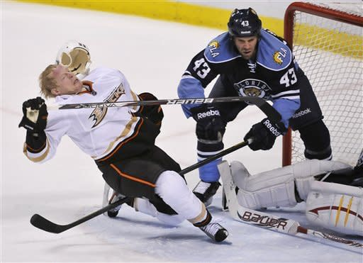 Anaheim Ducks' Jason Blake (33) loses his helmet as he is pulled from the goal by Florida Panthers' Mike Weaver (43) during the third period of an NHL hockey game on Sunday, Feb. 19, 2012, in Sunrise, Fla. The Ducks defeated the Panthers 2-0.(AP Photo/Gary I Rothstein)