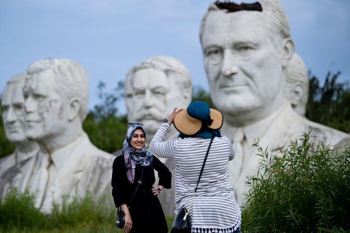 Zainab Jackson takes a photo of Ateeyeh Atefat in front of salvaged busts of former US Presidents August 25, 2019, in Williamsburg, Virginia. (Photo: Brendan Smialowski/AFP/Getty Images)