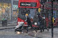 Pedestrians cross Oxford Street as the snow falls in London on January 24, 2021, as the capital experiences a rare covering of snow on Sunday. (Photo by JUSTIN TALLIS / AFP) (Photo by JUSTIN TALLIS/AFP via Getty Images)