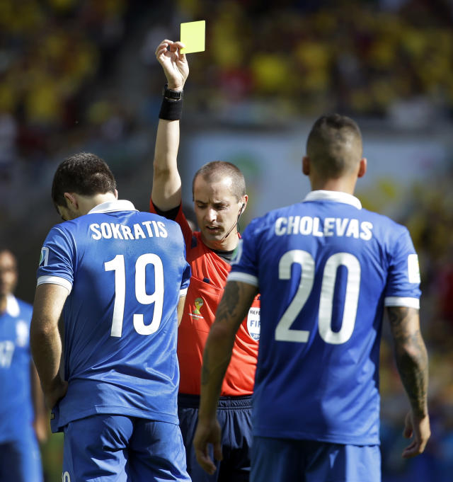 Greece's Sokratis Papastathopoulos (19) is given a yellow card by referee Mark Geiger from the United States during the group C World Cup soccer match between Colombia and Greece at the Mineirao Stadium in Belo Horizonte, Brazil, Saturday, June 14, 2014. Right is Greece's Jose Holebas. (AP Photo/Fernando Vergara)