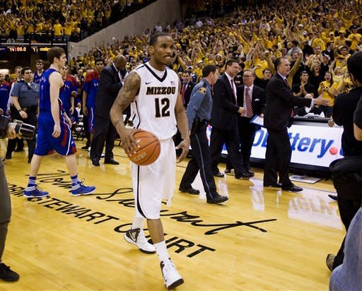 Missouri's Marcus Denmon, center, walks off the court with the ball after Missouri defeated Kansas 74-71 in an NCAA college basketball game on Saturday, Feb. 4, 2012, in Columbia, Mo. Missouri won the game 74-71. (AP Photo/L.G. Patterson)