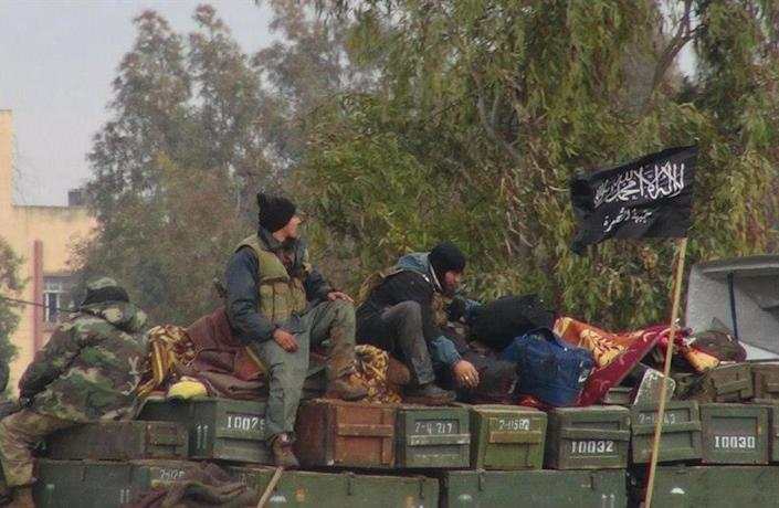 """FILE - In this Friday, Jan. 11, 2013 file citizen journalism image provided by Edlib News Network, ENN, which has been authenticated based on its contents and other AP reporting, shows rebels from al-Qaida affiliated Jabhat al-Nusra, as they sit on a truck full of ammunition, at Taftanaz air base, that was captured by the rebels, in Idlib province, northern Syria. The Arabic words on the flag, right, read:""""There is no God only God and Mohamad his prophet, Jabhat al-Nusra."""" Al-Nusra is an Islamist extremist group that has been behind some of the rebels' most significant battlefield successes. The U.S. has designated al-Nusra a terrorist organization, saying it is affiliated with the al-Qaida network. Al-Nusra has claimed responsibility for most of the deadliest suicide bombings targeting regime and military facilities. (AP Photo/Edlib News Network ENN, File)"""