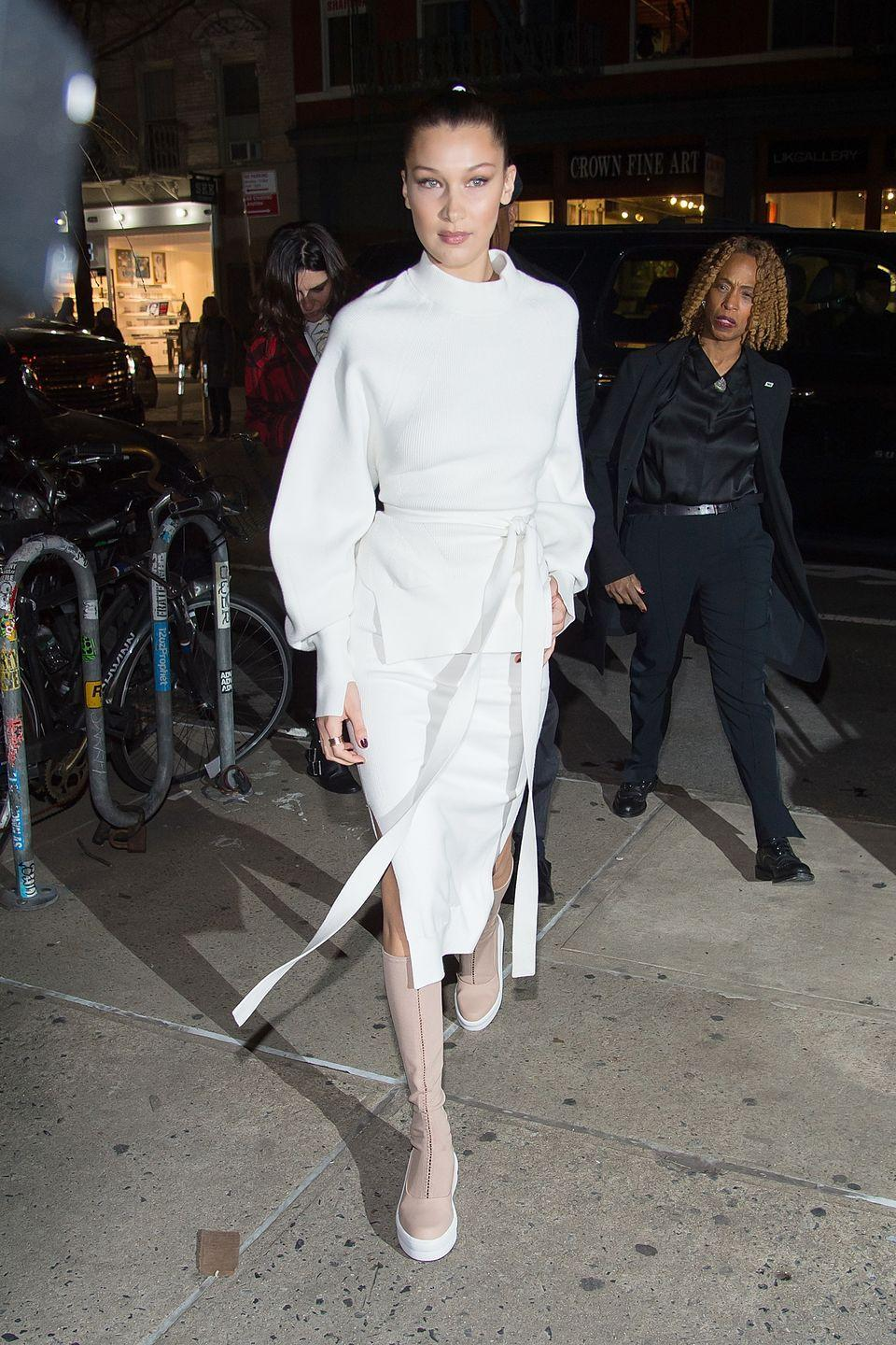 <p>In a DKNY white dress and knee-high beige boots while heading to her campaign launch at DKNY in New York. </p>