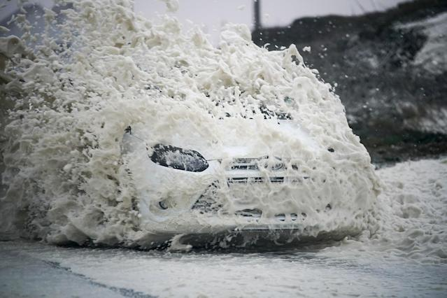 <p>A car drives through sea foam whipped up by the wind of Hurricane Ophelia at Trearddur Bay on Oct. 16, 2017 in Holyhead, Wales (Photo: Christopher Furlong/Getty Images) </p>