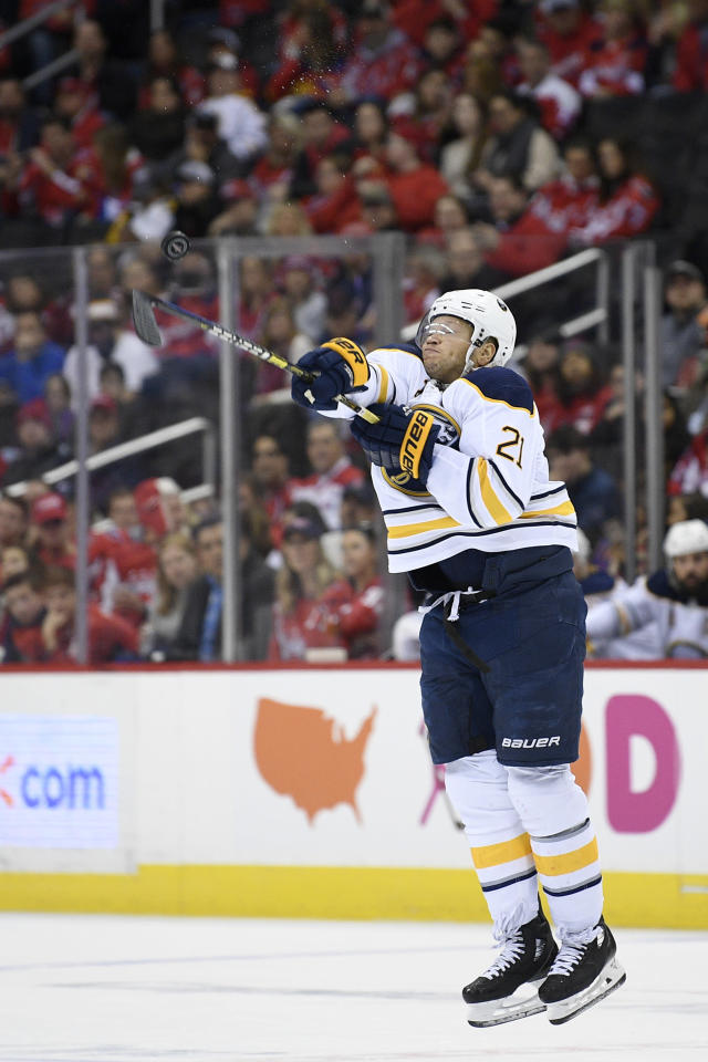 Buffalo Sabres right wing Kyle Okposo (21) swings at the airborne puck during the first period of an NHL hockey game against the Washington Capitals, Saturday, Dec. 15, 2018, in Washington. (AP Photo/Nick Wass)