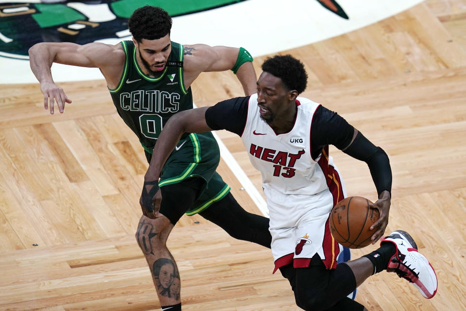 Miami Heat center Bam Adebayo (13) tries to outrun Boston Celtics forward Jayson Tatum (0) on a drive to the basket during the second half of an NBA basketball game Tuesday, May 11, 2021, in Boston. (AP Photo/Charles Krupa)
