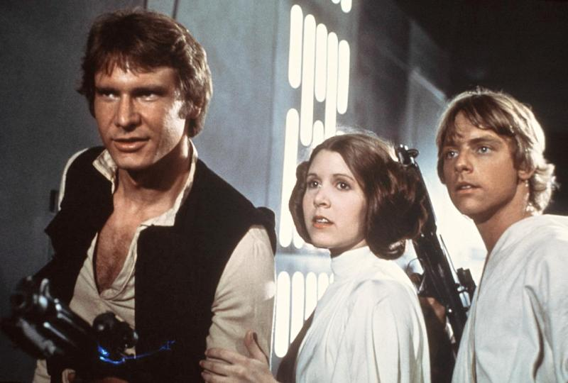 """In this 1977 image provided by 20th Century-Fox Film Corporation, from left, Harrison Ford, Carrie Fisher, and Mark Hamill are shown in a scene from """"Star Wars"""" movie released by 20th Century-Fox. (AP Photo/20th Century-Fox Film Corporation)"""