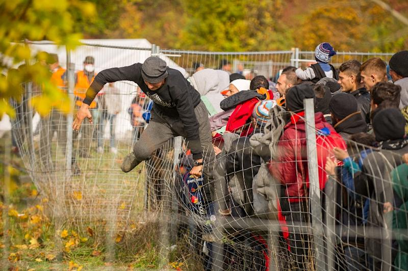 A man jumps over a fence as migrants walk to the Slovenian-Austrian border on October 25, 2015 (AFP Photo/Rene Gomolj)