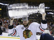FILE - In this Monday, June 24, 2013, file photo, Chicago Blackhawks defenseman Brent Seabrook hoists the Stanley Cup after the Blackhawks beat the Boston Bruins 3-2 in Game 6 of the NHL hockey Stanley Cup Finals in Boston. Longtime Chicago Blackhawks defenseman and three-time Stanley Cup winner Brent Seabrook announced Friday, March 5, 2021, he's unable to continue playing hockey because of injury. (AP Photo/Elise Amendola, File)