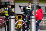 Protective Services Officers speak to a man on the first day of a five-day COVID-19 lockdown in Melbourne