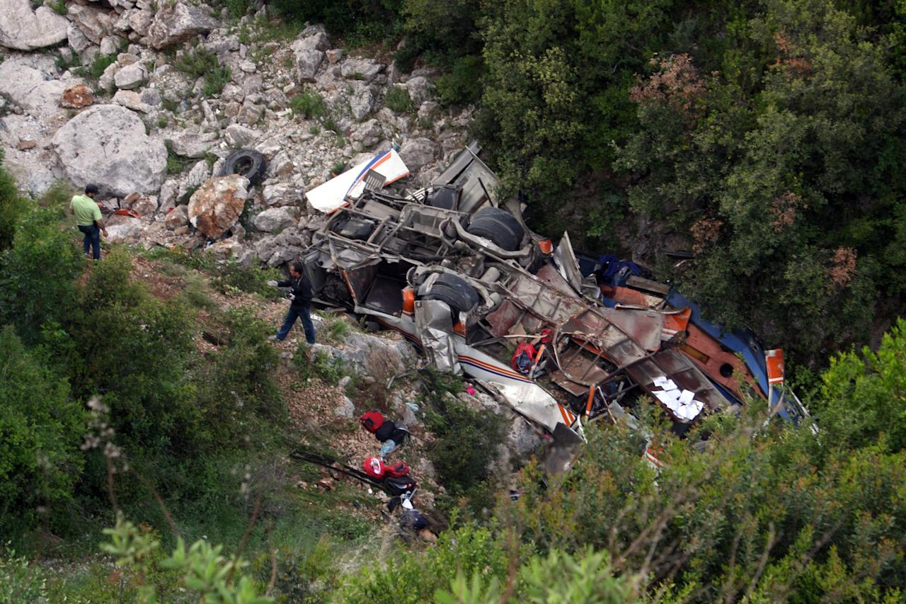 The bus that was carrying university students lies at the bottom of a cliff near Himare southern Albania on Monday, May 21, 2012 killing a number of people and injuring tens of others authorities said. Local prefect Edmond Velcani said the bus driver was among the people killed. The bus had been heading from the city of Elbasan to the southern city of Saranda. Police spokeswoman Klejda Plangarica said the bus fell some 80 meters (yards) off the road in Qafa e Vishes near the town of Himare, 137 miles (220 kilometers) south of the capital, Tirana, on Monday afternoon. (AP Photo)
