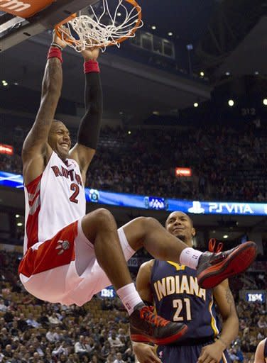 Toronto Raptors' James Johnson (2) hangs from the hoop after scoring as Indiana Pacers' David West looks on during first half NBA basketball action in Toronto, Friday, Jan. 13, 2012. (AP Photo/The Canadian Press, Chris Young)