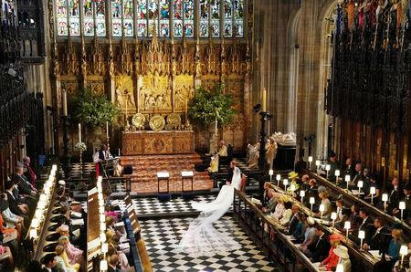 Prince Harry and Meghan Markle listen to an address by the Most Rev Bishop Michael Curry, primate of the Episcopal Church, in St George's Chapel at Windsor Castle during their wedding service in Windsor, Britain, May 19, 2018. Owen Humphreys/Pool via REUTERS