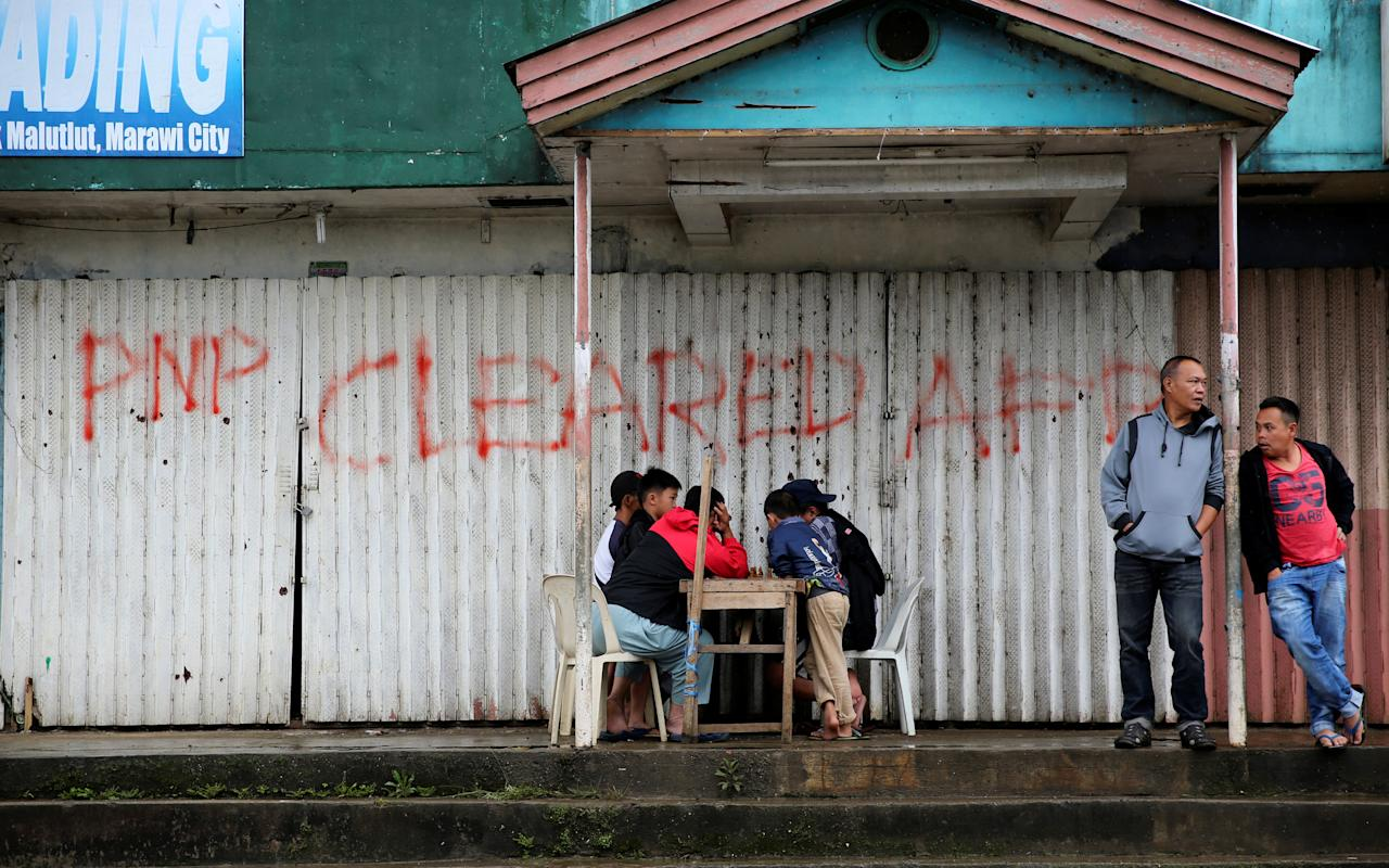 Residents play chess in front of a closed establishment with a sign declaring the area as cleared by government troops inside Marawi city, southern Philippines October 18, 2017. REUTERS/Romeo Ranoco