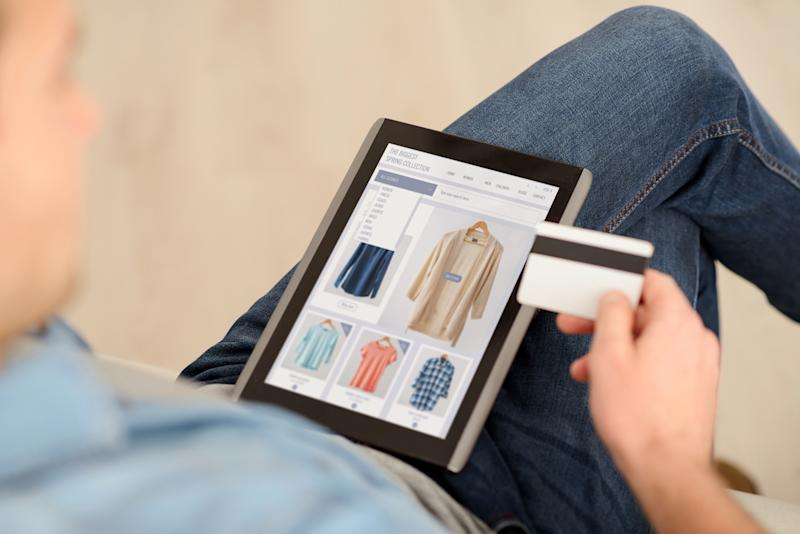 Man shops online with tablet while holding credit card in hand.