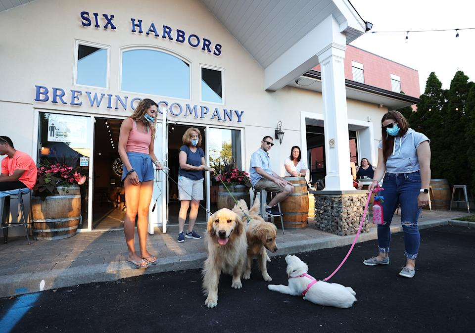 Owner Karen Heuwetter (L) introduces her golden retrievers Buddy and Barley to customers at the Six Harbors Brewing Company on June 24, 2020 in Huntington, New York. (Photo by Al Bello/Getty Images)