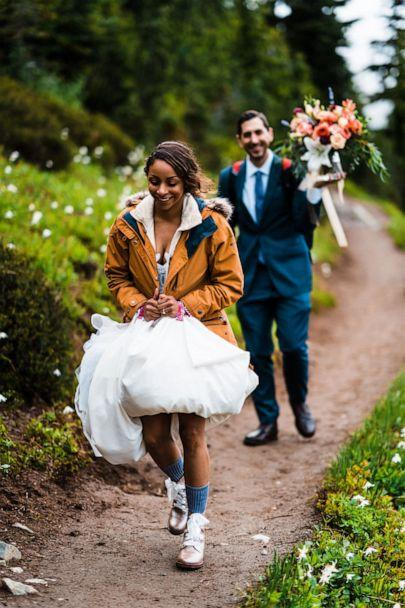 PHOTO: A bride holds her wedding dress while the groom holds the flowers during an adventure elopement. (Thefoxesphotography.com)
