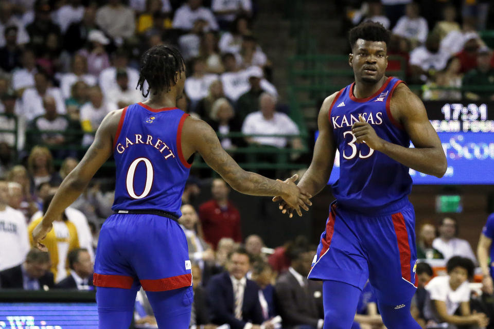 Kansas center Udoka Azubuike, right, low fives guard Marcus Garrett, left, after a made basket against Baylor during the second half of an NCAA college basketball game on Saturday, Feb. 22, 2020, in Waco, Texas. (AP Photo/Ray Carlin)