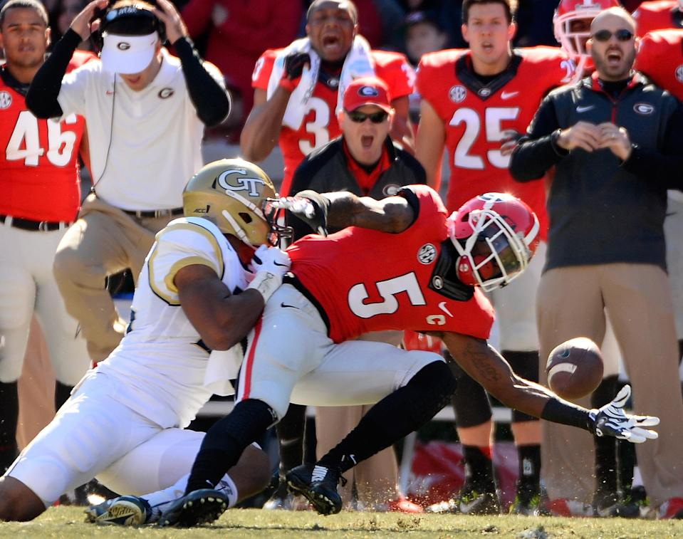 Georgia cornerback Damian Swann (5) almost intercepts a pass intended for Georgia Tech wide receiver DeAndre Smelter, left, during the first half of an NCAA college football game Saturday, Nov. 29, 2014, in Athens, Ga. (AP Photo/David Tulis)