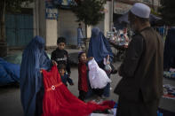 Afghan women and a girl shop for dresses at a local market in Kabul, Afghanistan, Friday, Sept. 10, 2021. (AP Photo/Felipe Dana)