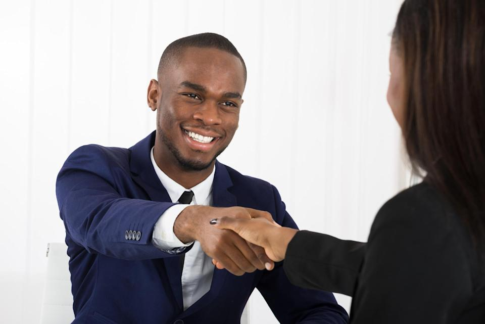 Man in suit shaking hands with woman