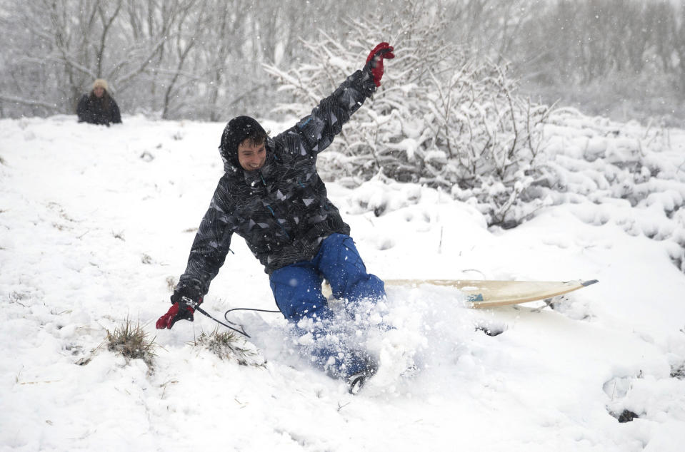 A man uses a surf board to sledge down a snow covered hill in Wye National Nature Reserve near Ashford, southern England, Sunday Feb. 7, 2021. Heavy snow is predicted to bring widespread disruption to many areas of England as cold winds grip much of the nation. (Andrew Matthews/PA via AP)
