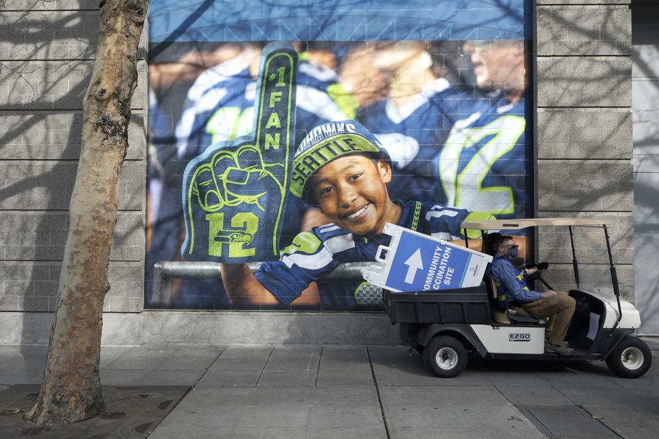 """FILE - A cart carries a sign that reads """"Community Vaccination Site,"""" past a photo of a Seattle Seahawks fan, on the first day of operation of a mass COVID-19 vaccination site at the Lumen Field Events Center in Seattle, which adjoins the field where the NFL football Seahawks and the MLS soccer Seattle Sounders play their games, in this Saturday, March 13, 2021, file photo. All 32 teams are conducting open practices on Saturday, July 31, as part of """"Back Together Saturday."""" Some teams will be offering COVID-19 vaccinations at their facilities. (AP Photo/Ted S. Warren, File)"""