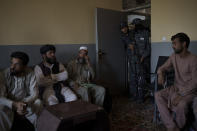 Afghan men sit in the criminal cases room of a police station in Kabul, Afghanistan, Sunday, Sept. 19, 2021. The Taliban are shifting from being warriors to an urban police force. (AP Photo/Felipe Dana)