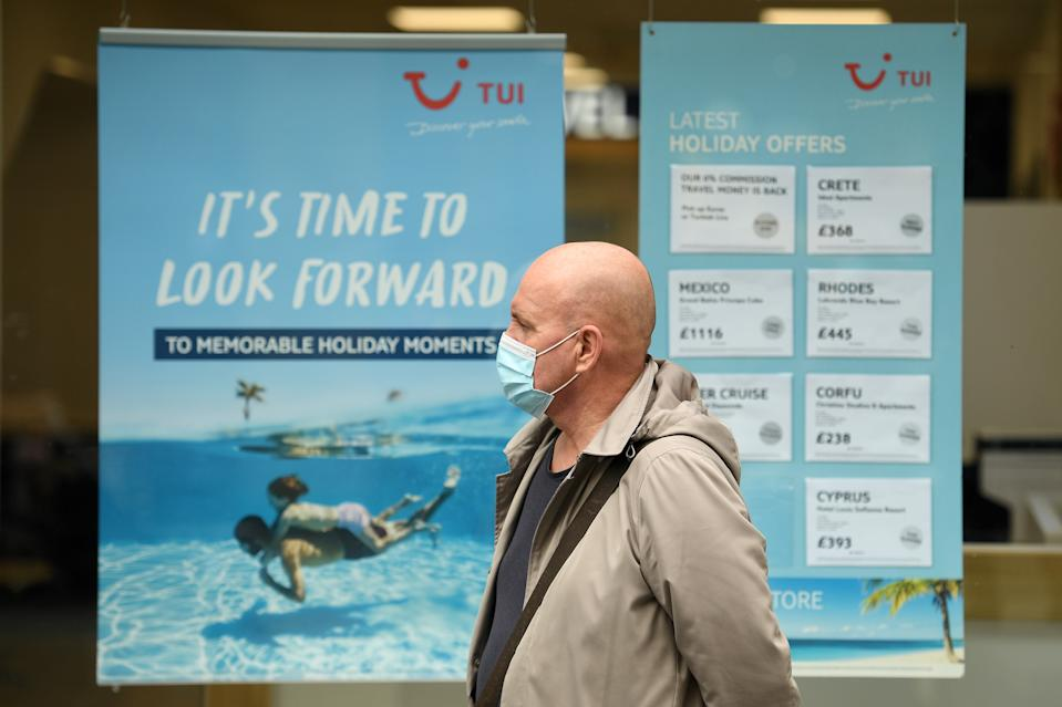 A man wearing a face mask or covering due to the COVID-19 pandemic, walks past the window of a TUI travel agent's holiday shop in Liverpool, north west England on October 2, 2020, following the  announcement of new local restrictions for certain areas in the northwest of the country, due to a resurgence of novel coronavirus cases. - The British government on Thursday extended lockdowns to Liverpool and several other towns in northern England, effectively putting more than a quarter of the country under tighter coronavirus restrictions. Health Secretary Matt Hancock said limits on social gatherings would be extended to the Liverpool City region, which has a population of about 1.5 million. (Photo by Oli SCARFF / AFP) (Photo by OLI SCARFF/AFP via Getty Images)