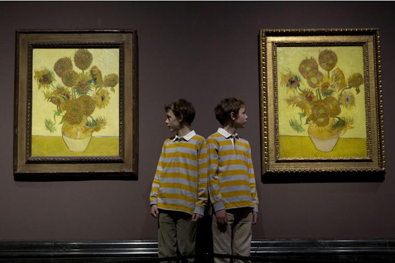 "Twins Edgar, left, and Gabriel, aged 10, pose for photographers beside two versions of Dutch-born painter Vincent van Gogh's ""Sunflowers"", the left one from 1888 and the right one from 1889, during a photocall at the National Portrait Gallery in London, Friday, Jan. 24, 2014. The two paintings are being reunited in London for the first time in 65 years, with the 1889 version on loan from the Van Gogh Museum in Amsterdam. They will be displayed together until April 27. (AP Photo/Matt Dunham)"