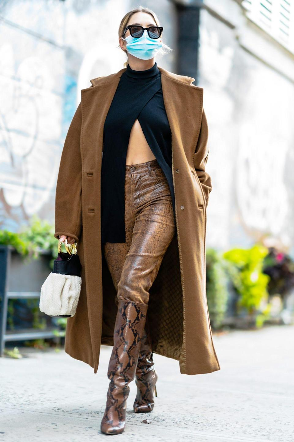 <p>Ashley Benson wears snakeskin boots and matching leather trousers while walking through N.Y.C. on Monday. </p>