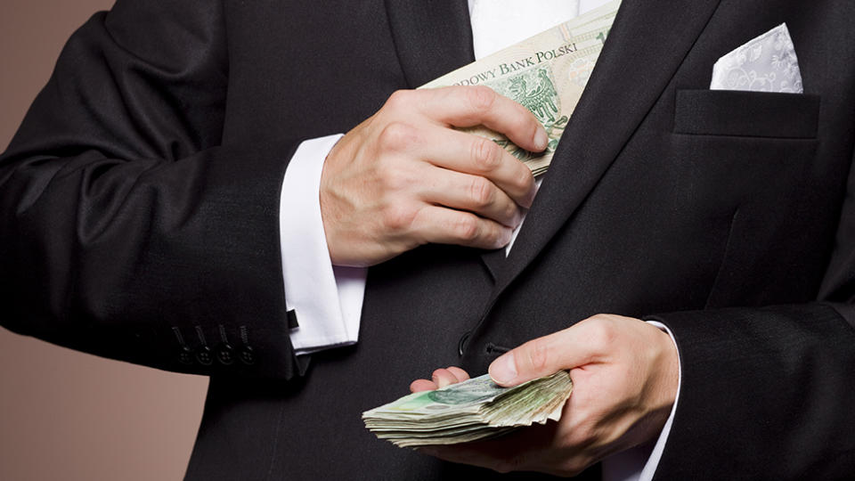 Groom pockets cash from handful representing bride and groom's cash grab