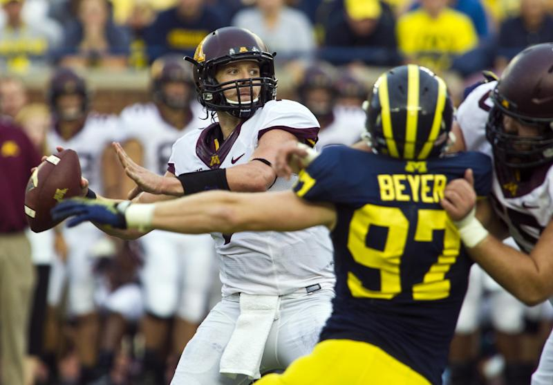 Minnesota quarterback Mitch Leidner (7) looks to throw a pass under pressure from Michigan linebacker Brennen Beyer (97) in the fourth quarter of an NCAA college football game, Saturday, Oct. 5, 2013, in Ann Arbor, Mich. Michigan won 42-13. (AP Photo/Tony Ding)