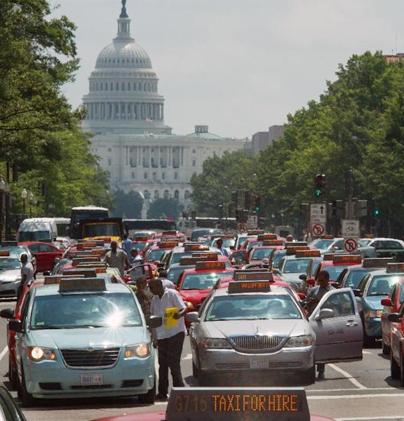 Taxi drivers park their cars in protest on Pennsylvania Avenue bringing street traffic to a stop, as they demand an end to ride sharing services such as Uber X and Lyft on June 25, 2014, in Washington, DC (AFP Photo/Paul J. Richards)