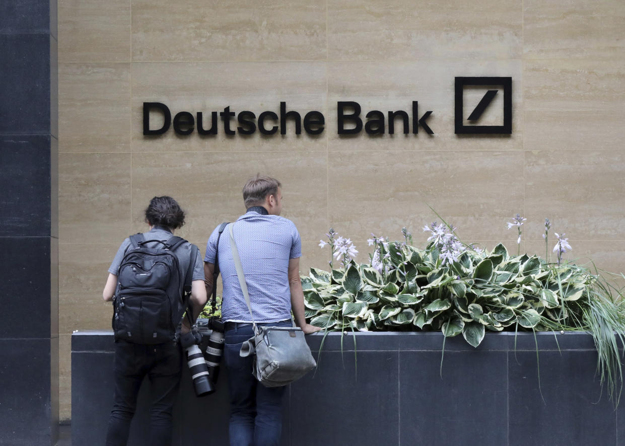 """Journalists outside Deutsche Bank building in London, Monday, July, 8, 2019.  Germany's struggling Deutsche Bank says it will cut 18,000 jobs by 2022,  saying it is going """"back to our roots"""" with a radical restructuring plan meant to focus the company on traditional strengths.(AP Photo/Natasha Livingstone)"""