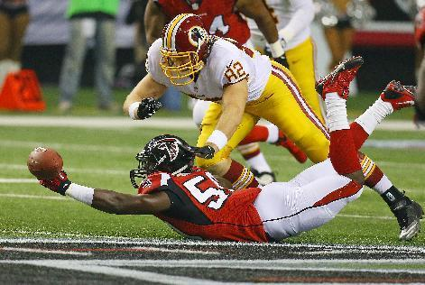 Atlanta Falcons linebacker Joplo Bartu, bottom, nearly intercepts a pass from Washington Redskins quarterback Kirck Cousins to tight end Logan Paulsen (82) as it bounces off his hand during first-half action in an NFL football game on Sunday, Dec. 15, 2013, in Atlanta. (AP Photo/Atlanta Journal-Constitution, Curtis Compton)
