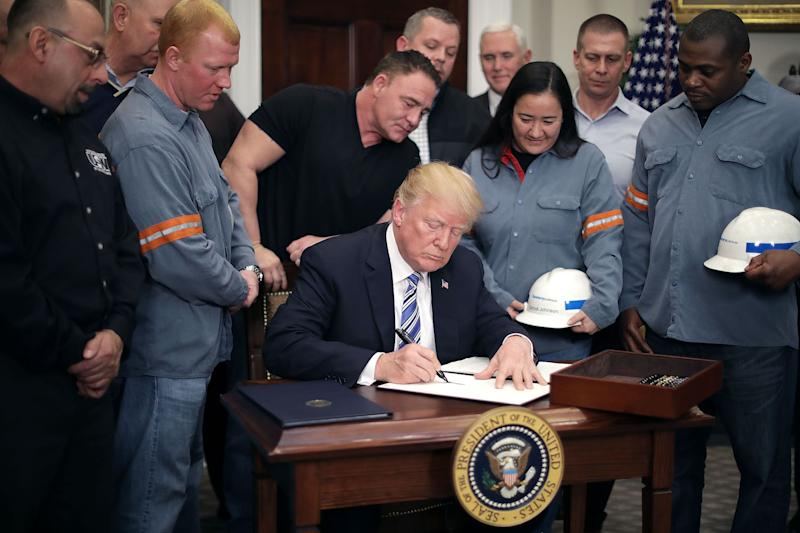 Surrounded by steel and aluminum workers, President Trump signs a 'Section 232 Proclamation' on steel imports in the White House on March 8. (Getty)