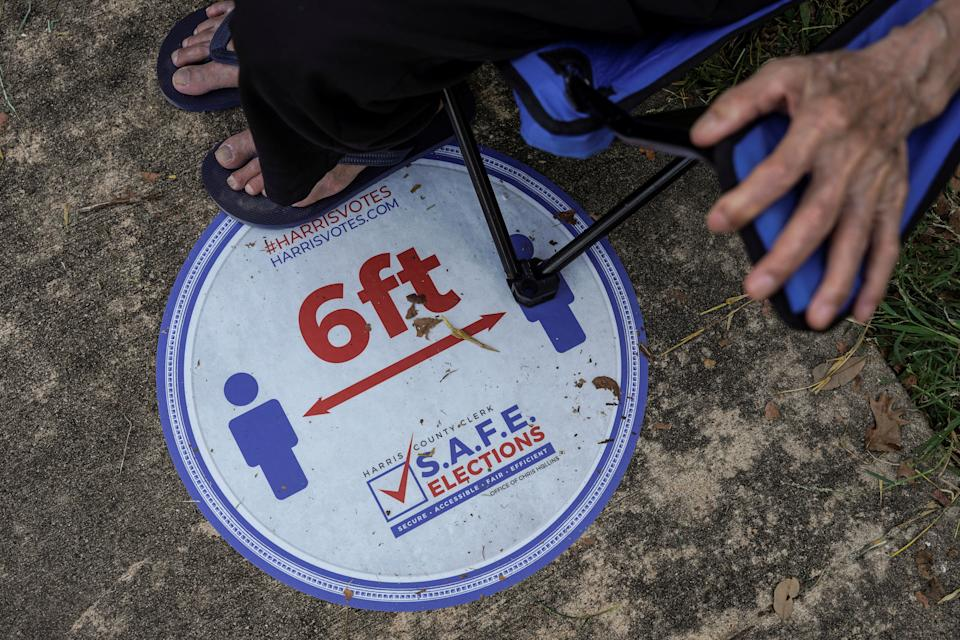 A sign to remind voters on social distancing is placed on a floor as person sits on a portable chair while waiting in line to cast his ballot for the upcoming presidential election as early voting begins in Houston, Texas, U.S., October 13, 2020.  REUTERS/Go Nakamura