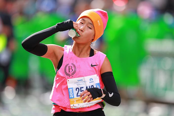 A participant folds a cup to take a drink of water during the 2019 New York City Marathon. (Photo: Gordon Donovan/Yahoo News)