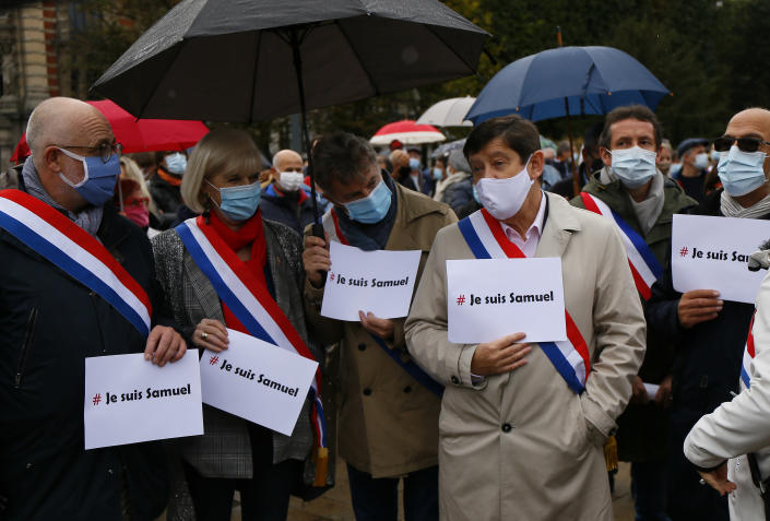 """Communist party parliament member Fabien Roussel, third left, and his deputy stand with posters that read: """"I am Samuel"""", as people gather on Republique square in Lille, northern France, Sunday Oct. 18, 2020. Demonstrators in France on Sunday took part in gatherings in support of freedom of speech and in tribute to a history teacher who was beheaded near Paris after discussing caricatures of Islam's Prophet Muhammad with his class. (AP Photo/Michel Spingler)"""