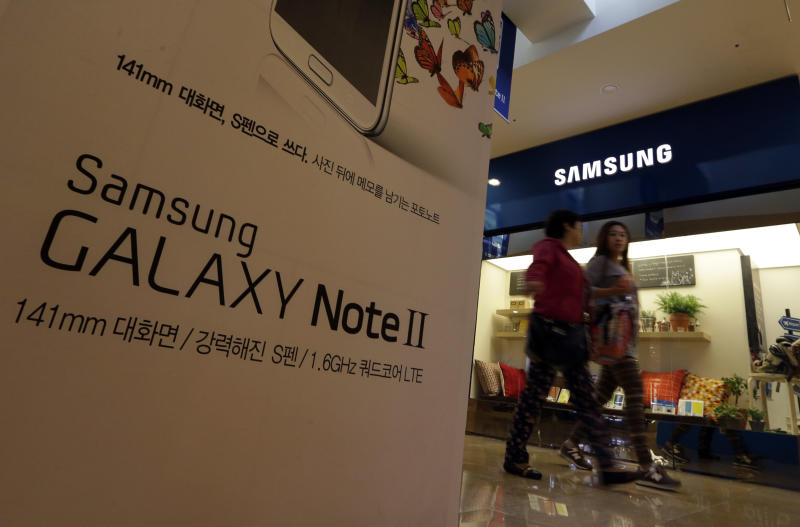 Visitors walk by the billboard of Samsung Electronics's Galaxy Note II at a showroom of its headquarters in Seoul, South Korea, Friday, Oct. 26, 2012. Samsung's third-quarter net profit nearly doubled over a year earlier to a record high propelled by strong sales of Galaxy phones that helped widen its lead over rivals. (AP Photo/Lee Jin-man)