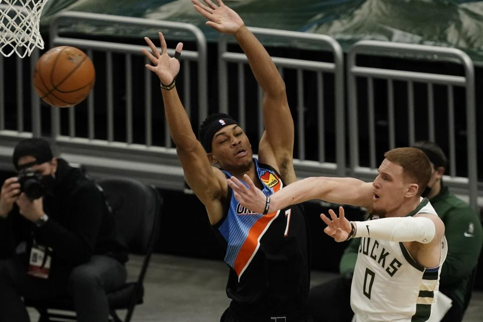 Milwaukee Bucks' Donte DiVincenzo passes around Oklahoma City Thunder's Darius Bazley during the first half of an NBA basketball game Friday, Feb. 19, 2021, in Milwaukee. (AP Photo/Morry Gash)