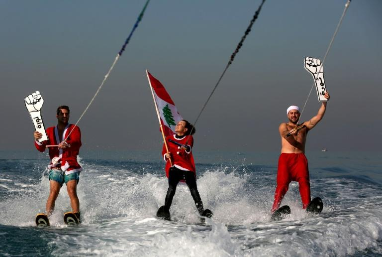 """Lebanese water skiers dressed wave a national flag and raise cardboard fists reading """"Revolution"""" in support of anti-government protests in the bay of Jounieh north Beirut (AFP Photo/PATRICK BAZ)"""