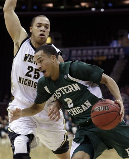 Eastern Michigan's J.R. Sims (2) drives past Western Michigan's David Brown (25) in the first half during an NCAA college basketball game at the Mid-American Conference men's tournament on Thursday, March 14, 2013, in Cleveland. (AP Photo/Tony Dejak)