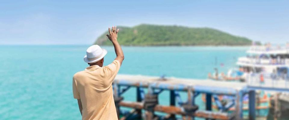 The traveler man standing on the boat waving his hand, greeting or goodbye to their friends on the pier.