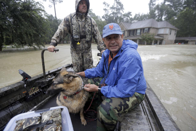<p>Joe Garcia, right, and his dog Heidi ride in Murphy Fire Department's Todd Herrington's boat after being rescued from his flooded home as floodwaters from Tropical Storm Harvey rise, Aug. 28, 2017, in Spring, Texas. (Photo: David J. Phillip/AP) </p>