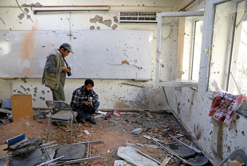 FILE PHOTO: Afghan journalists film inside a class after yesterday's attack at the university of Kabul