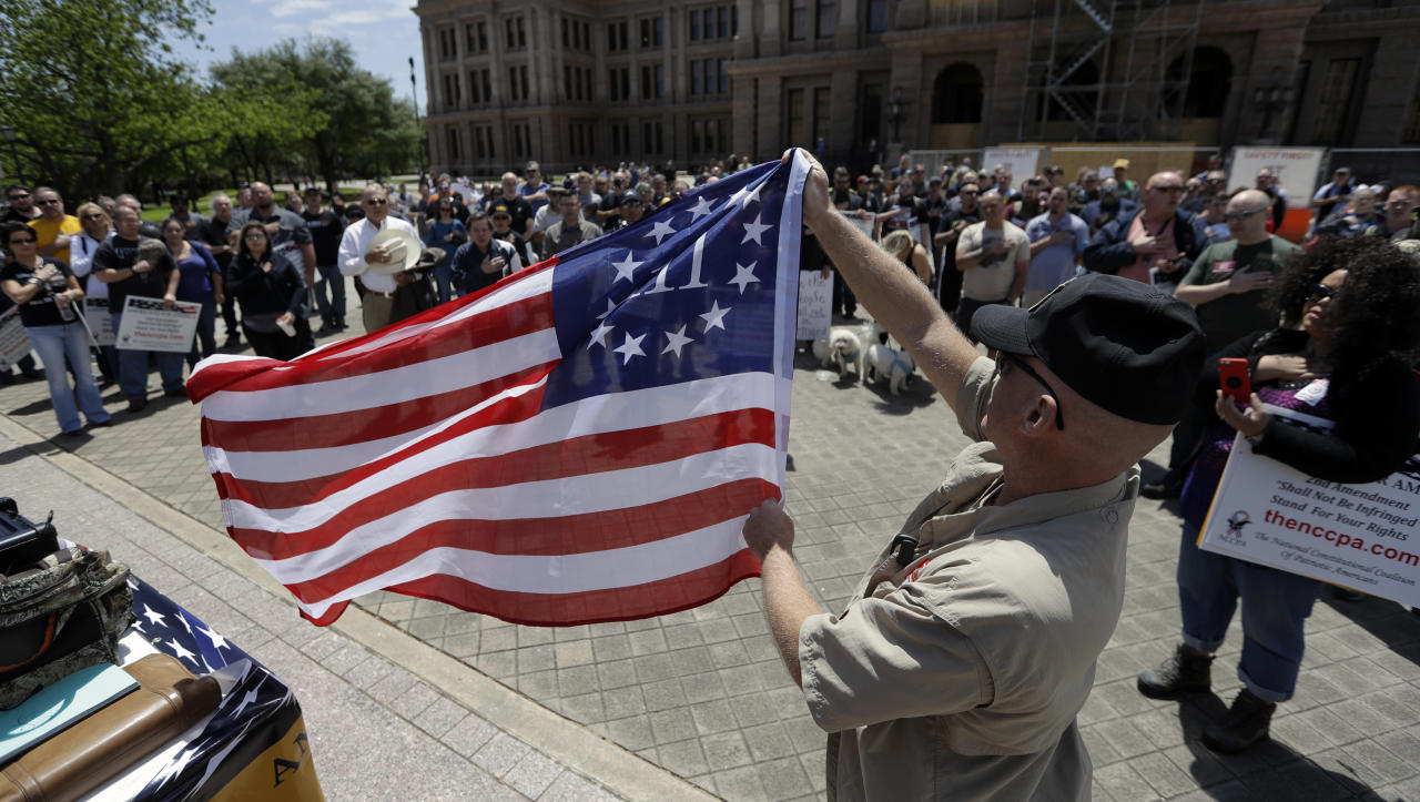 <p>A man holds a 3% flag as a group recited the pledge during a pro gun-rights rally at the state capitol, Saturday, April 14, 2018, in Austin, Texas. (Photo: Eric Gay/AP) </p>