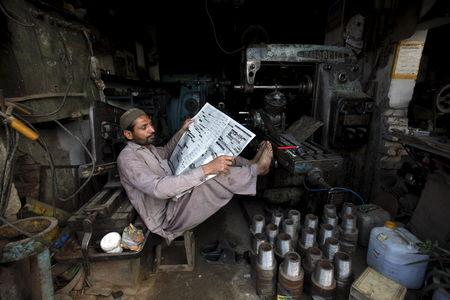 A worker takes a break from his work during a power cut at a workshop on the outskirts of Peshawar